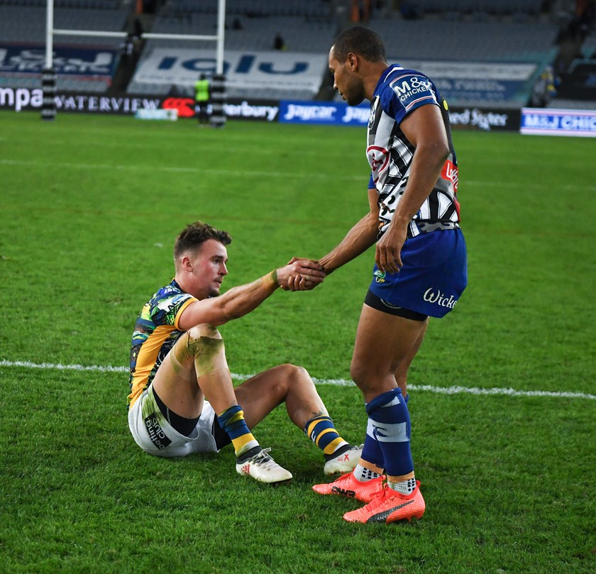 Bulldogs fullback Moses Mbye offers a hand to Eels fullback Clint Gutherson.