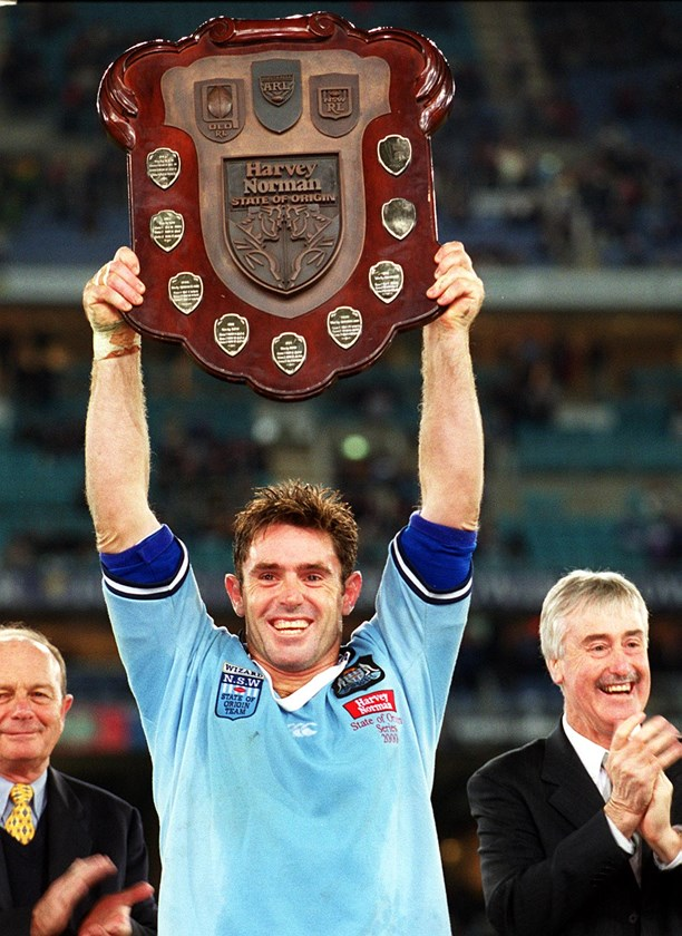 Brad Fittler holds the shield aloft after NSW won the 2000 series.