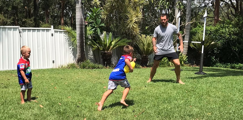 Cooper and Jaxon play backyard footy with their dad, David Klemmer.