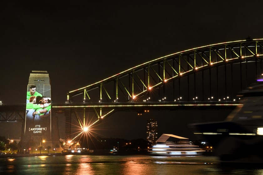 Sydney Harbour Bridge is lit up with Raiders images on Monday night.