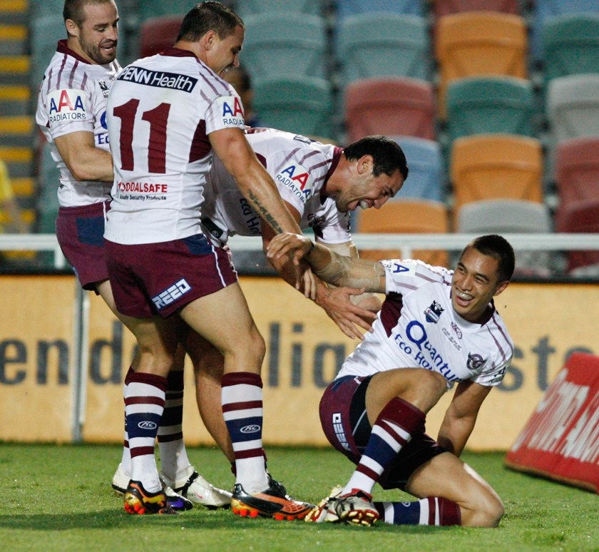 Dean Whare is swamped by Manly teammates after scoring in his NRL debut against the Cowboys.