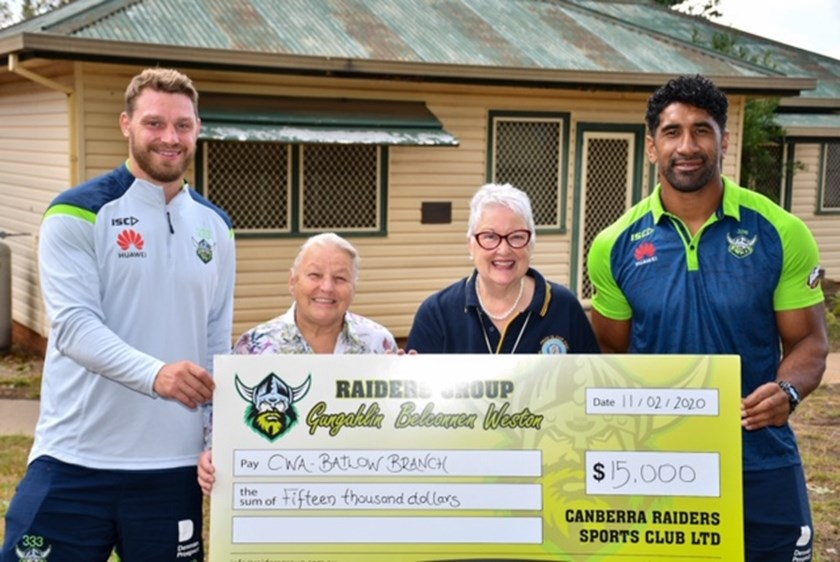 Elliott Whitehead and Sia Soliola present a cheque to the Batlow Country Women's Association.