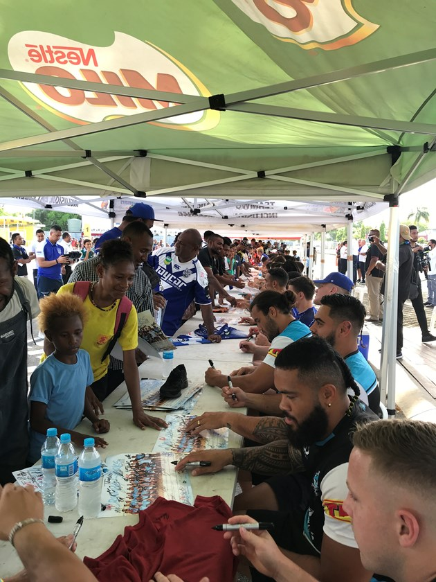 Sharks and Bulldogs players sign autographs from fans in Port Moresby.