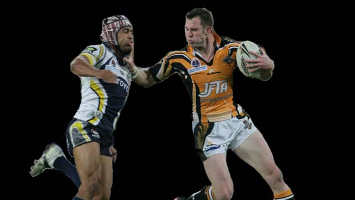 Wests Tigers Pat Richards fends North Queensland's Rod Jensen in the 2005 Grand Final.