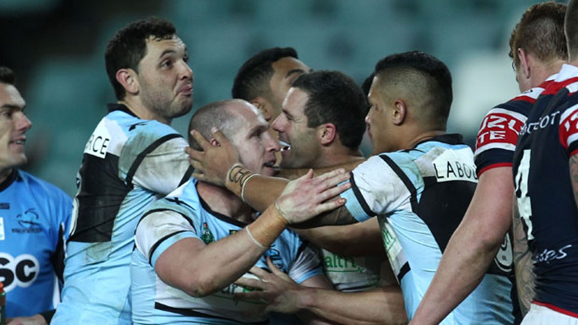 Sharks halfback Jeff Robson is mobbed by teammates after scoring the match-winning try against the Roosters on Saturday night.