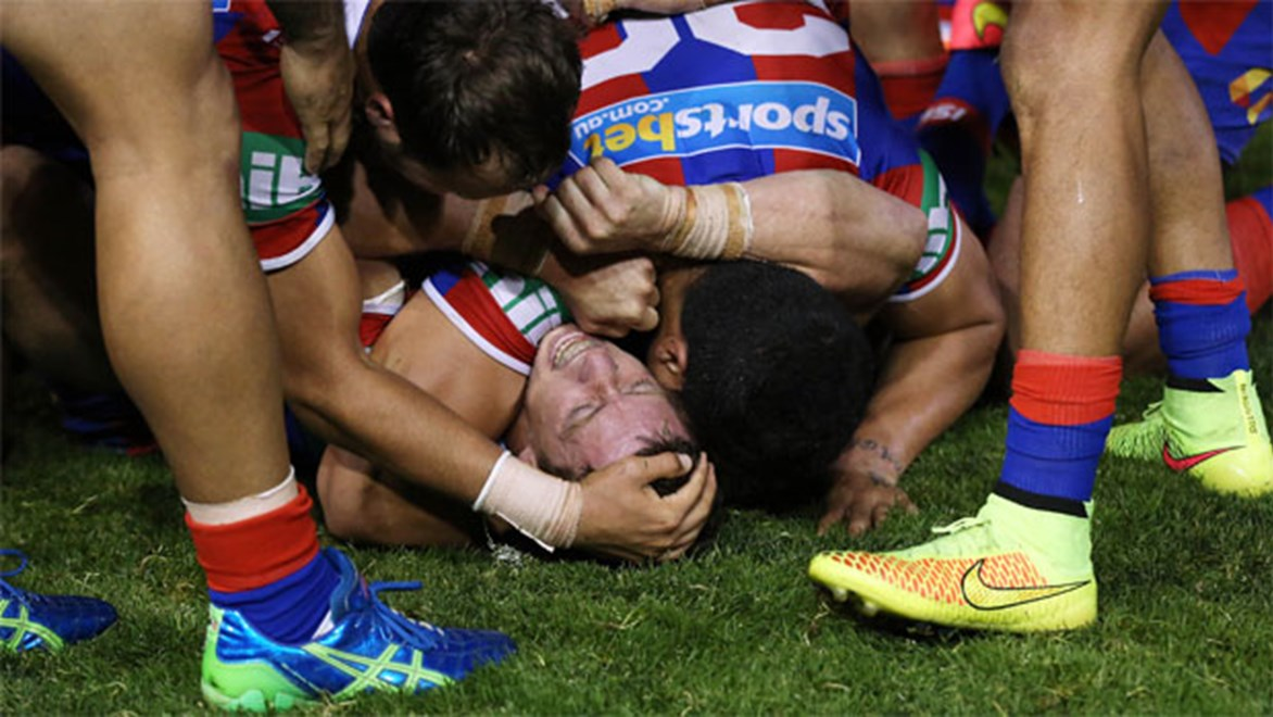 Knights captain Kurt Gidley is mobbed by teammates after kicking an after-the-siren sideline conversion to beat the Storm 32-30 in Round 22.