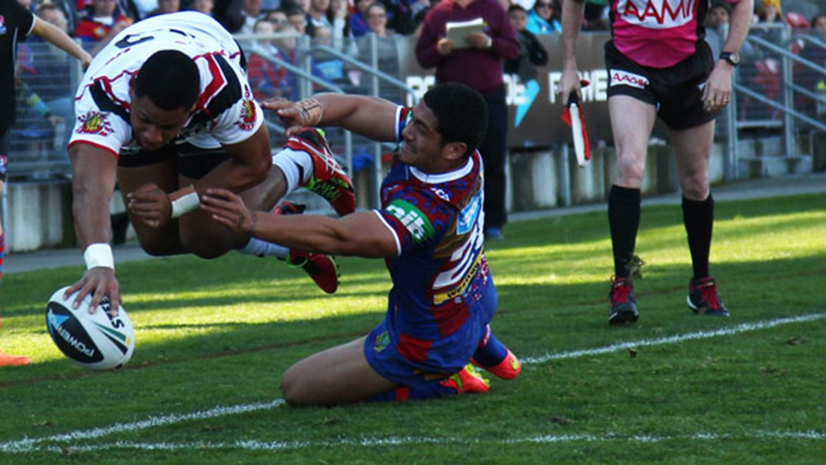 Warriors winger David Fusitu'a defies gravity to ground the ball for a try against the Knights on Sunday.
