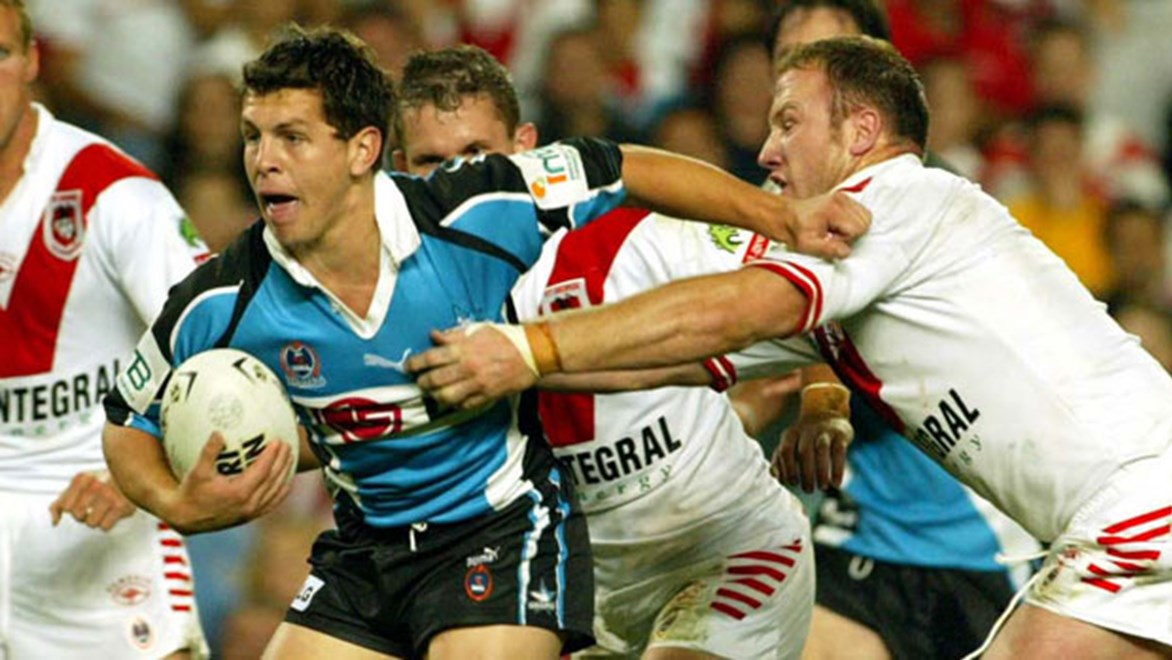 Greg Bird fends off current Titans teammate Luke Bailey in the first NRL game he ever won with the Sharks, the 2002 Semi-Final against St George Illawarra.