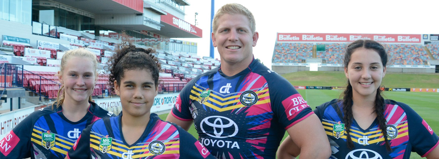 Prop Ben Hannant models the Cowboys' Women in League jersey along with Townsville under-14 players Erin Tremblett, Izabella Kennedy and Maddison Craigie.