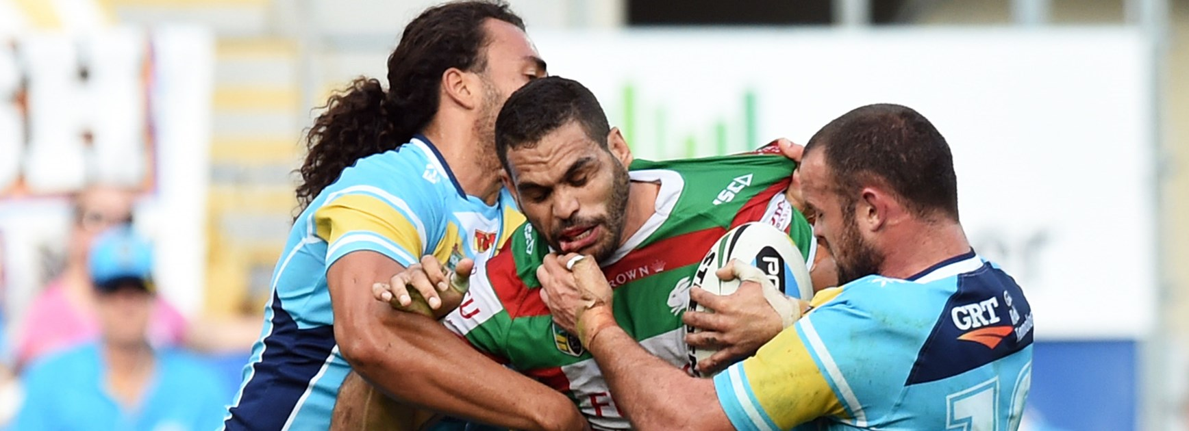 Greg Inglis is tackled by Titans forwards Ryan James and Nate Myles on Saturday.