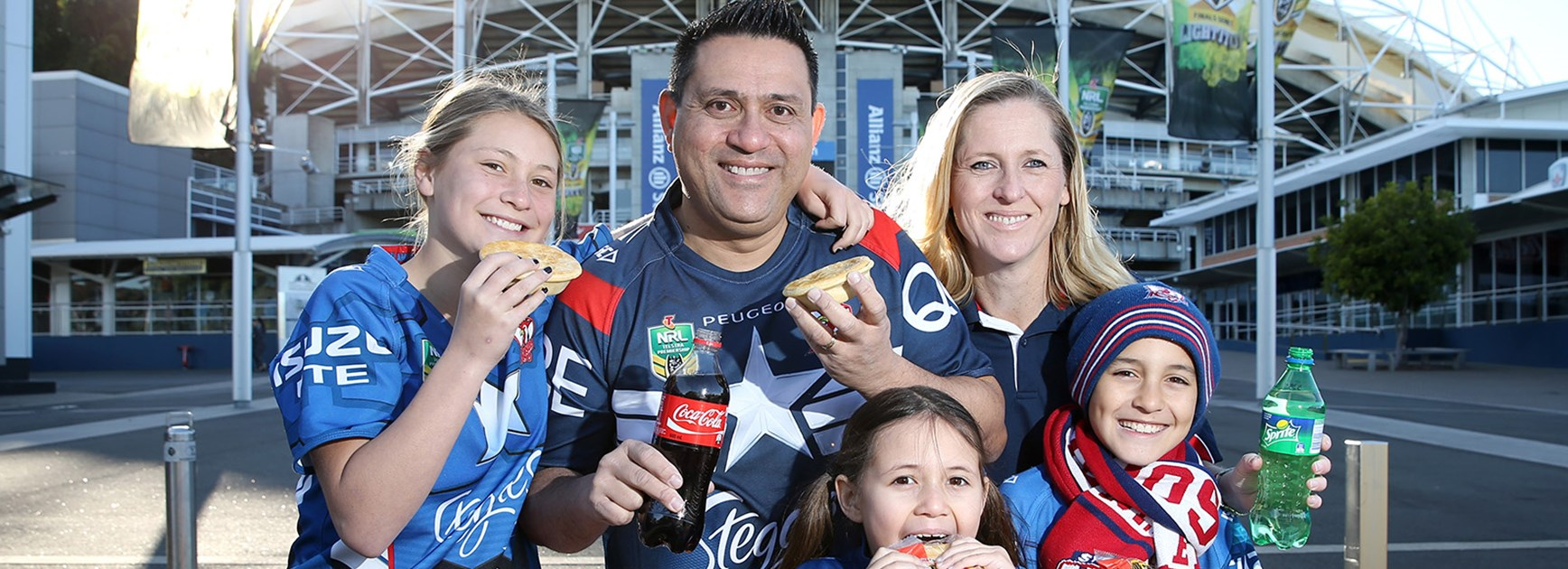 The Joseph family, Nellie, Josh, Alex, Lottie and Lenny, enjoy a pie and drink at Allianz Stadium.