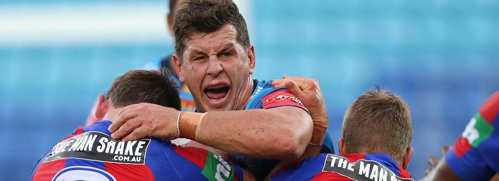 Titans lock Greg Bird in action against the Knights in Round 1.