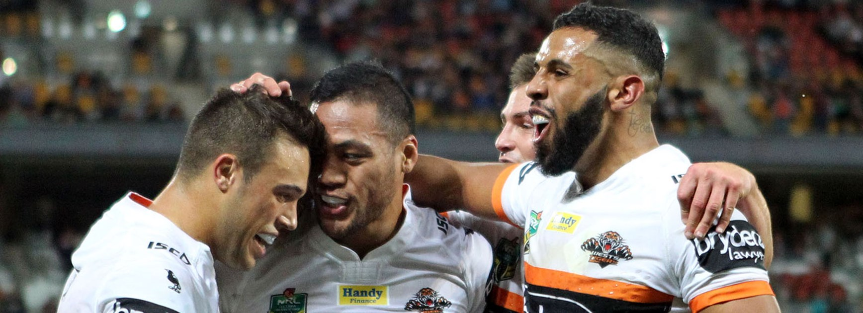The Wests Tigers celebrate a try to Tim Simona against the Broncos at Suncorp Stadium.
