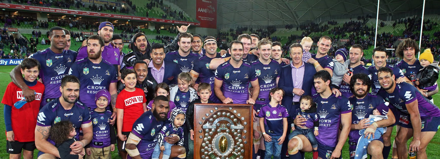 Storm players celebrate with the JJ Giltinan Shield following their win over the Sharks.