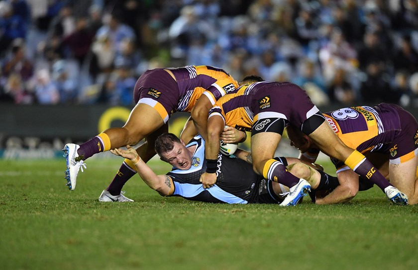 Paul Gallen feels the effects of a Broncos tackle.