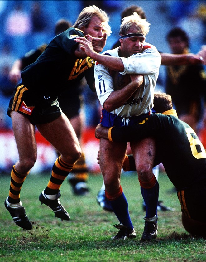 Great Britain forward Mike Gregory tries to shrug off Kangaroos halfback Peter Sterling  and five-eighth Wally Lewis in 1988.
