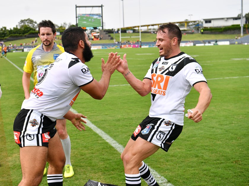 Josh Reynolds congratulates Magpies teammate Bilal Maarbani on scoring a try.